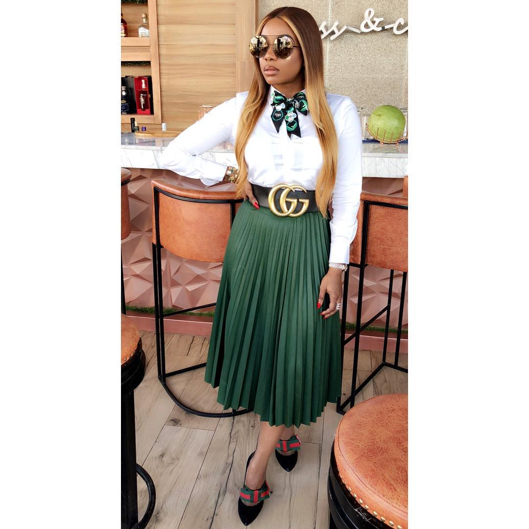 chioma good hair in an amazing looking white top and green flaring long shirt. dabbled in a Gucci shoe