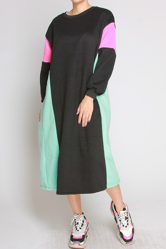 Model rocking black fashion in the fleece-lined color block dress by Liz. Colors are black, pink, and sea green.