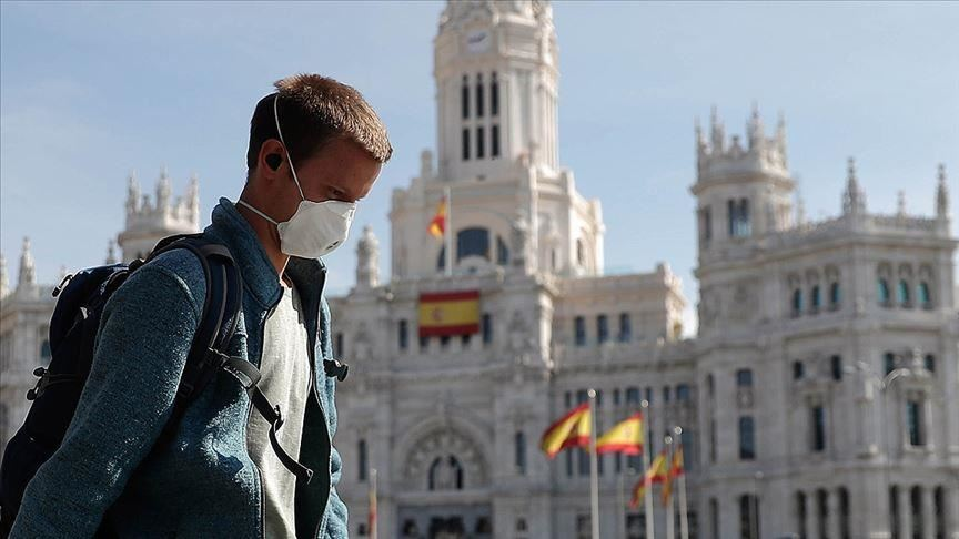 Man in nose mask walking past the Plaza de Cibeles