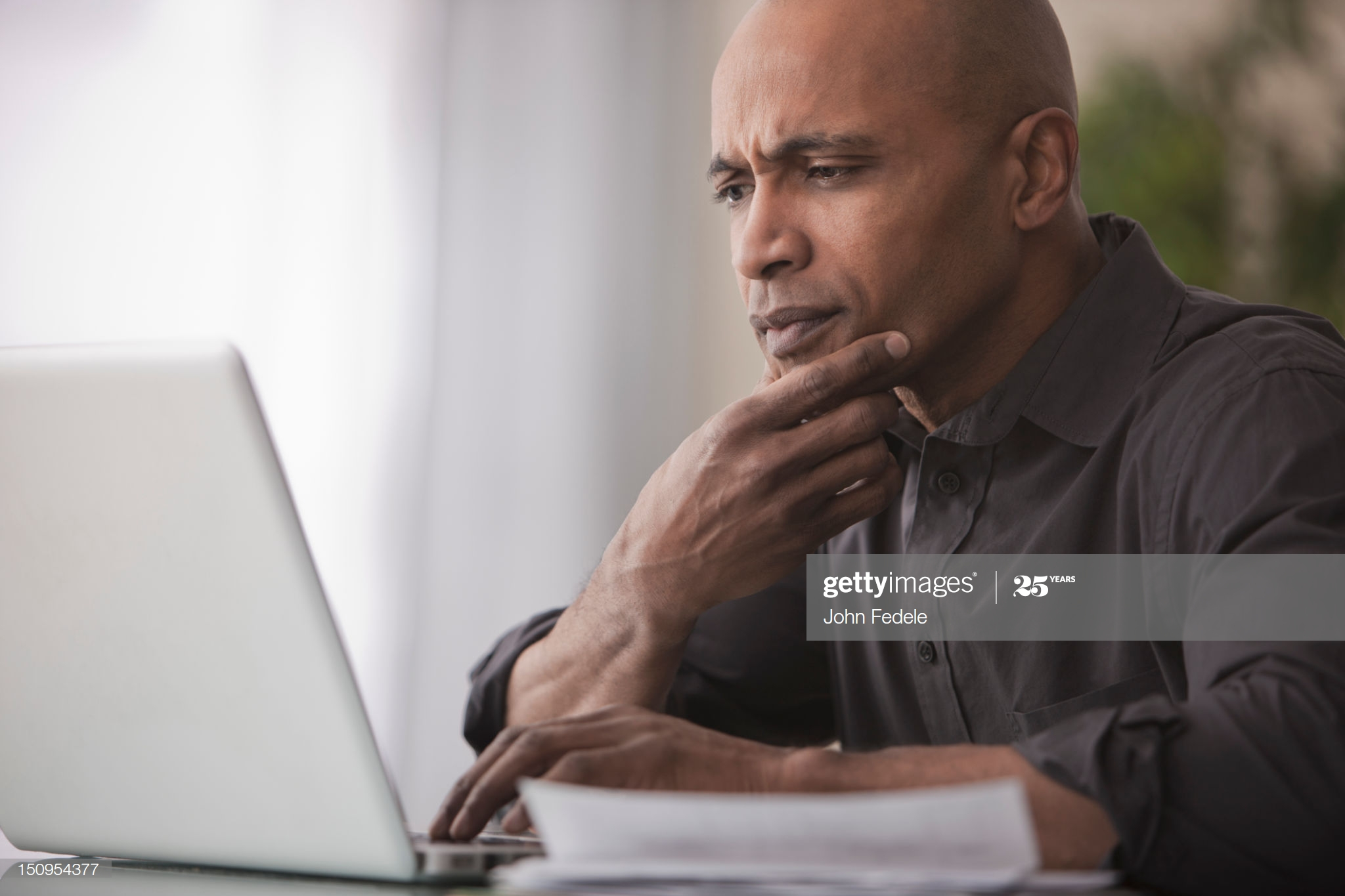 black man worrying confused computer starring
