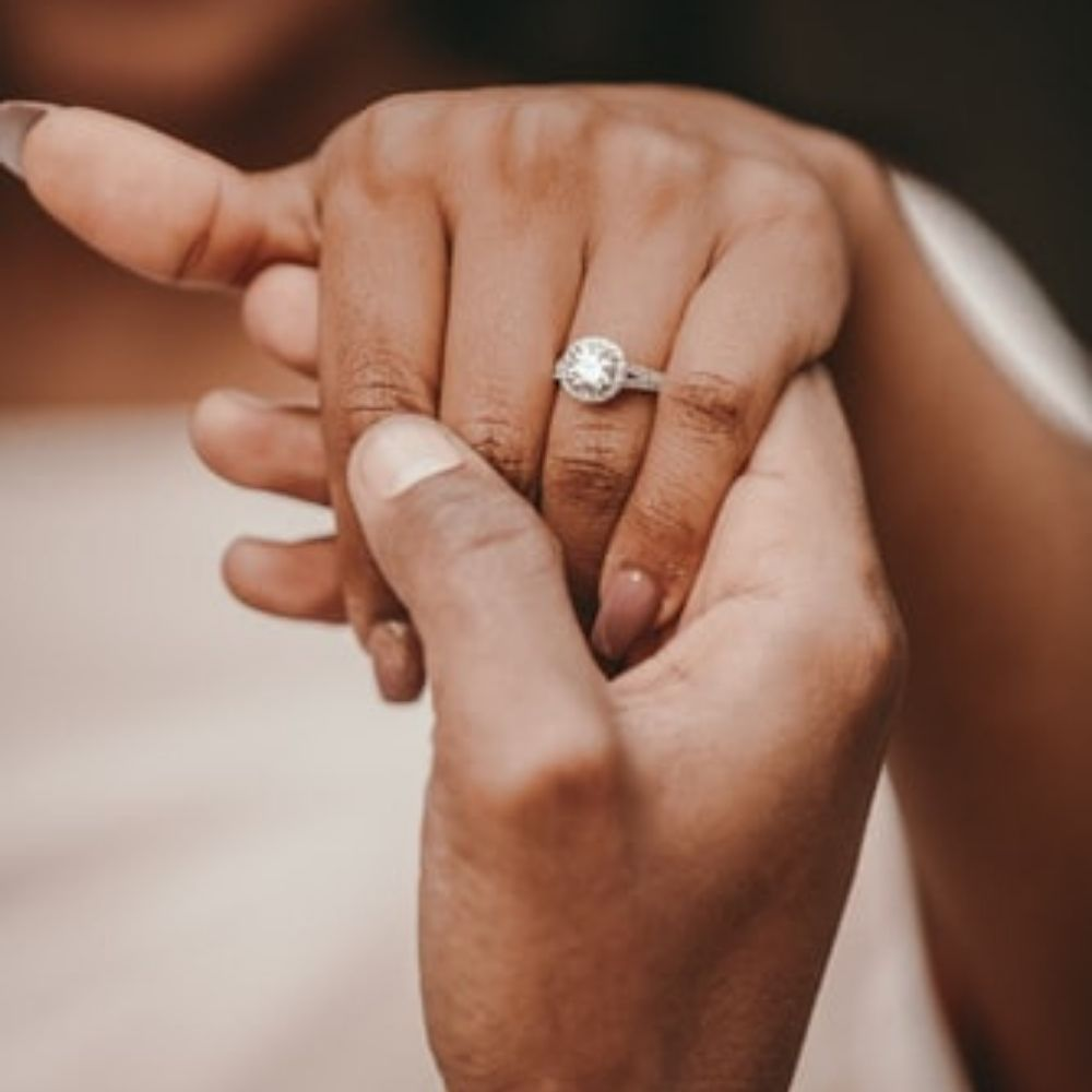 woman-wearing-diamond-engagement-ring-buying-man-hand-holding-hers