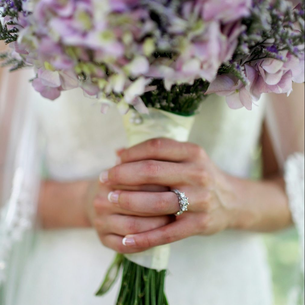 woman-holding-flower-showing-3-stone-carat-ring-difference